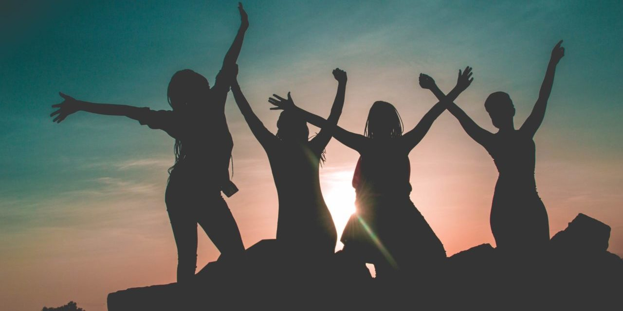 Silhouette of four women with sun background