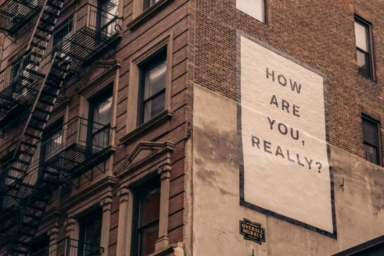 "Brown Building with Sign ""How Are You Really?"""