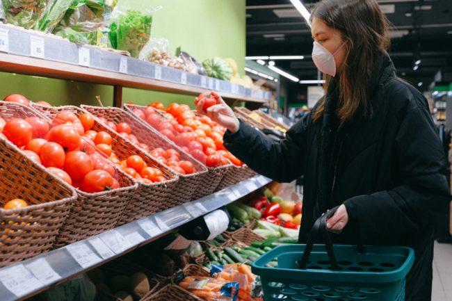woman wearing mask and buying food in supermarket during coronavirus pandemic
