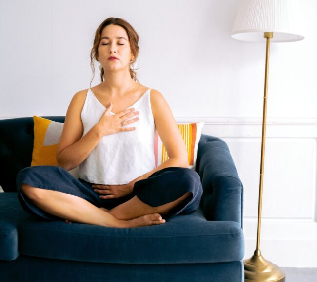 woman practicing breathing on couch