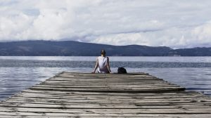woman sitting on dock by water